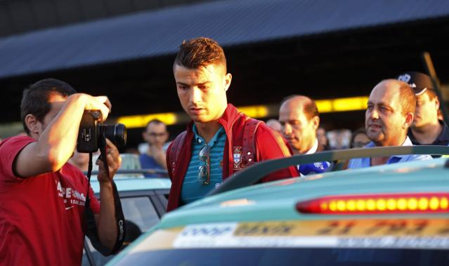 Portugal's Cristiano Ronaldo (C) prepares to enter a taxi after returning from the 2014 World Cup in Brazil with the national soccer team, at Lisbon airport June 28, 2014. REUTERS/Hugo Correia (PORTUGAL - Tags: SPORT SOCCER WORLD CUP)