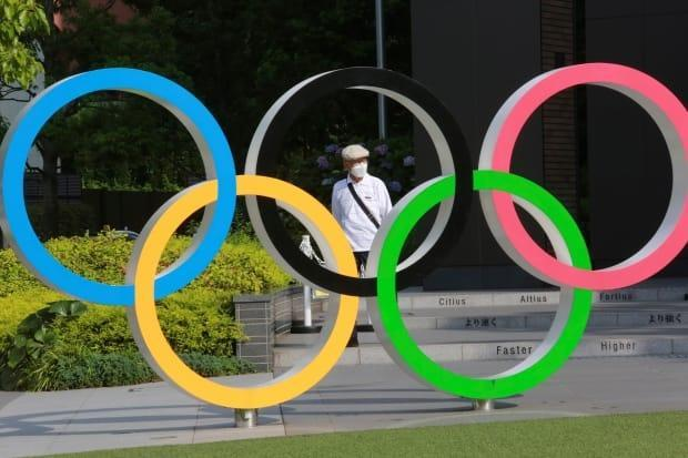 A man walks past the Olympic rings in Tokyo on Monday. Despite a year-long delay caused by the coronavirus pandemic, the 2020 Summer Games are scheduled to open in the Japanese capital on July 23. (Koji Sasahara/The Associated Press - image credit)