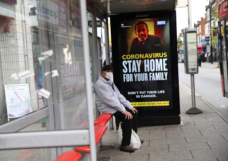 A man wearing a protective face mask waits in a bus stop in East Ham, east London, as the UK continues in lockdown to help curb the spread of the coronavirus. Picture date: Tuesday April 28, 2020.