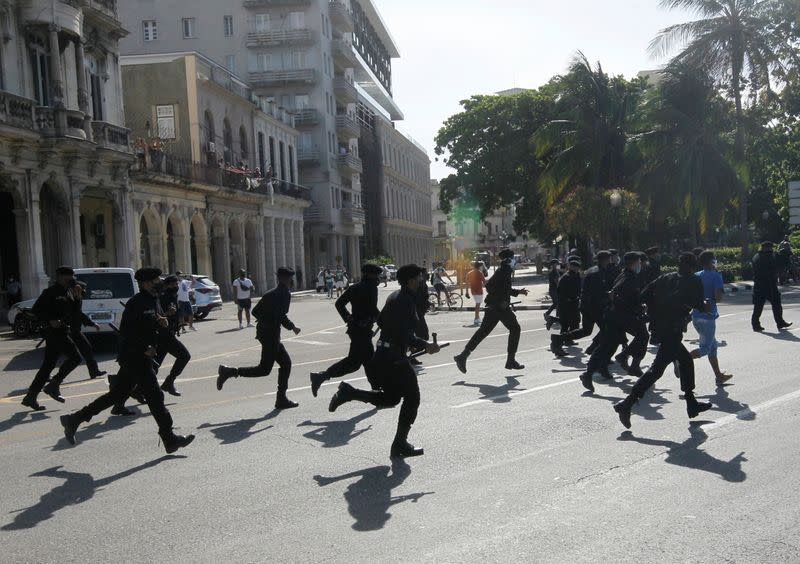 Police run during protests against and in support of the government, in Havana