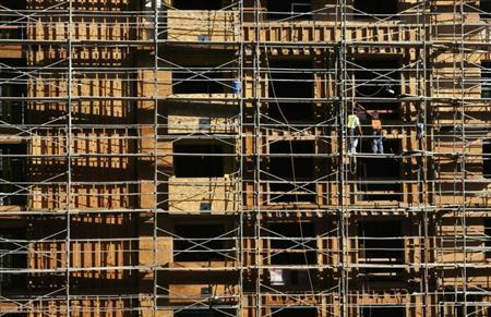 Construction workers stand on scaffolding at an apartment building under construction in Hollywood