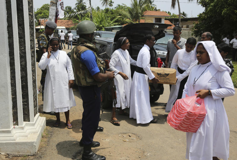 Catholic nuns and priests carry food packets to distribute to security personnel standing guard at St. Sebastian Church in Negombo, Sri Lanka Thursday, April 25, 2019. The U.S. Embassy in Sri Lanka warned Thursday that places of worship could be targeted for militant attacks over the coming weekend, as police searched for more suspects in the Islamic State-claimed Easter suicide bombings that killed over 350 people.(AP Photo/Manish Swarup)