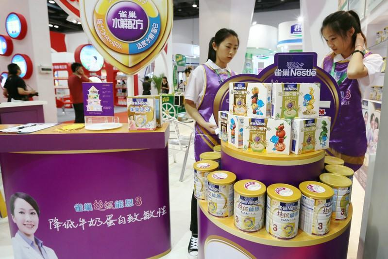 FILE PHOTO: Staff members are seen at the booth of Nestle promoting its baby food at a maternity and baby industry fair in Beijing