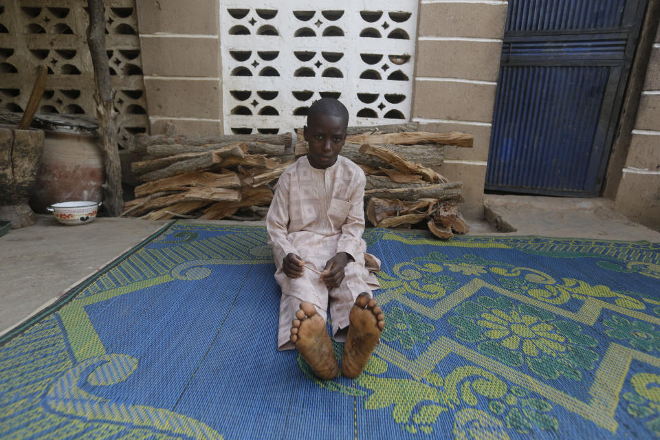 Usman Mohammad Rabiu, a 13 year old student of Government Science Secondary School Kankara, sits in his family house in Ketare, Nigeria, and speaks to the Associated Press, Saturday Dec. 19, 2020. Nigeria's freed schoolboys have reunited with their joyful parents after being held captive for nearly a week by gunmen allied with jihadist rebels in the country's northwest. Relieved parents hugged their sons tightly on Saturday in Kankara, where more than 340 boys were abducted from the Government Science Secondary school on the night of Dec. 11. (AP Photo/Sunday Alamba)