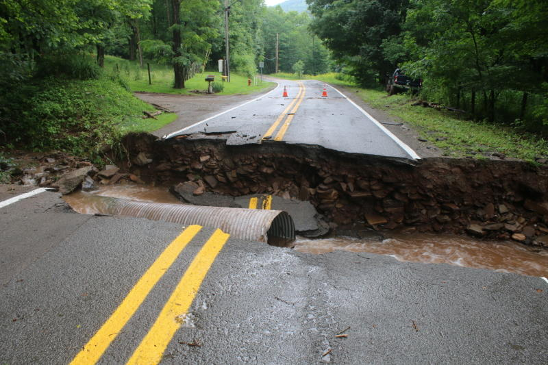 A road is washed out in the Harman area of Randolph County, W.V., Sunday, June 30, 2019. Severe thunderstorms caused flash flooding that knocked homes off their foundations and washed out roads in several mountainous counties of West Virginia, and some state lawmakers asked Gov. Jim Justice on Sunday to declare a state of emergency. (Destiny Judy/Daily Inter-Mountain via AP)