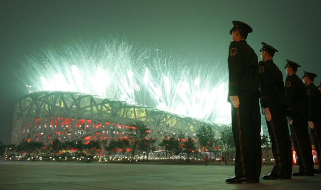 Police officers stand guard as fireworks explodes during the opening ceremony in the National Stadium at the Beijing 2008 Olympics in Beijing, Friday, Aug. 8, 2008. (AP Photo/Charlie Riedel)