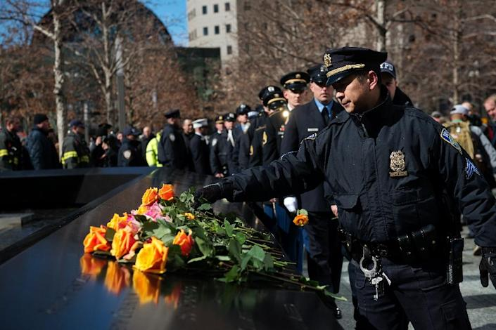 New York Police Department members lay roses on the 9/11 Memorial on the 23rd Anniversary of the 1993 World Trade Center bombing on February 26, 2016 (AFP Photo/Bryan Thomas)