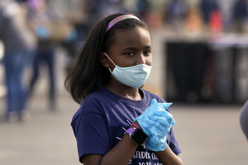 Zoey Arthurs, 9, wears a mask and gloves while volunteering at a food distribution center set up at SoFi Stadium ahead of Thanksgiving and amid the COVID-19 pandemic, Monday, Nov. 23, 2020, in Inglewood, Calif. (AP Photo/Marcio Jose Sanchez)