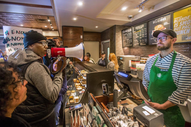 In this April 15, 2018, file photo, Asa Khalif, left, a Black Lives Matter activist from Philadelphia, demands the firing of a Starbucks cafe manager who called police, resulting in the arrest of two black men Thursday, April 12, 2018, at the Starbucks cafe in Philadelphia. The two men, Rashon Nelson and Donte Robinson, settled with the city of Philadelphia for a symbolic $1 each Wednesday, May 2, 2018, and a promise from city officials to set up a $200,000 program for young entrepreneurs. Starbucks will close its stores in the U.S. on the afternoon of Tuesday, May 29, to hold racial bias training for all of its employees. (Mark Bryant/The Philadelphia Inquirer via AP)