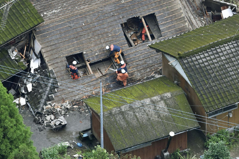 Rescuers work on the rooftop of the house damaged by a landslide in Soo, Kagoshima prefecture, western Japan, Thursday, July 4, 2019. Japanese authorities on Wednesday directed more than 1 million residents in parts of the southern main island of Kyushu to evacuate to designated shelters as heavy rains batter the region, prompting fears of landslides and widespread flooding.(Kyodo News via AP)