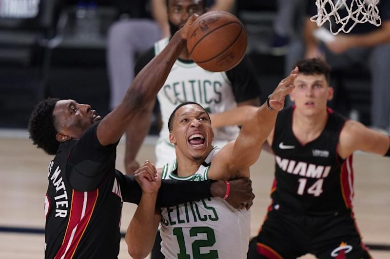 Miami Heat's Bam Adebayo, left, and Boston Celtics' Grant Williams (12) battle for a rebound during the second half of an NBA conference final playoff basketball game Sunday, Sept. 27, 2020, in Lake Buena Vista, Fla. (AP Photo/Mark J. Terrill)