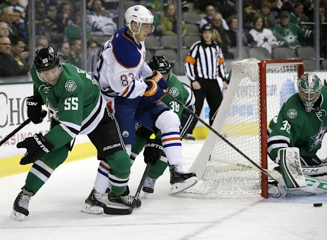Dallas Stars' Sergei Gonchar (55) of Russia and Vernon Fiddler (38) help with pressure from Edmonton Oilers right wing Ales Hemsky (83) of Czech Republic as Stars goalie Kari Lehtonen prepares to glove a loose puck in the second period of an NHL Hockey game, Tuesday, Jan. 14, 2014, in Dallas. (AP Photo/Tony Gutierrez)
