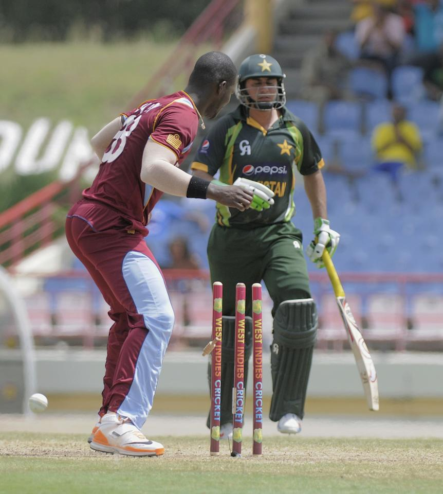 Pakistan batsman Nasir Jamshed (R) run out by Chris Gayle off West Indies bowler Darren Sammy (L) for 23 runs during the 5th and final ODI West Indies v Pakistan at Beausejour Cricket Ground on July 24, 2013 in Gros Islet, St. Lucia.  The score was , WI 242/7, Pak 65/2 (18 ov). AFP PHOTO/RANDY BROOKS        (Photo credit should read RANDY BROOKS/AFP/Getty Images)