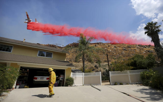 <p>Riverside City Fire Department Engineer Peter Habib stands outside a home to help provide structure protection as a plane drops fire retardant on a hillside during the Marlborough fire on Thursday, Aug. 31, 2017 in Riverside, Calif. (Photo: Stan Lim/The Press-Enterprise via AP) </p>