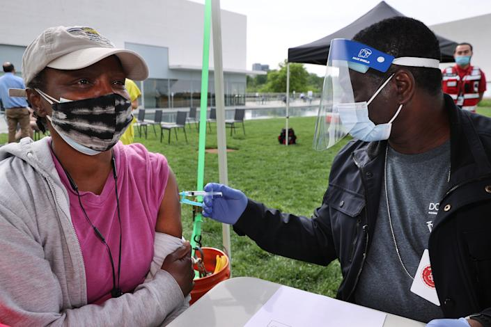 WASHINGTON, DC - MAY 06: Darlene Grant (L) receives a dose of the Johnson & Johnson coronavirus vaccine during a walk-up clinic at the Kennedy Center for the Performing Arts' outdoor Reach area on May 06, 2021 in Washington, DC. Hosted by the District of Columbia Health Department, the event also provided newly vaccinated people with a free beer courtesy of Solace Brewing Co. (Photo by Chip Somodevilla/Getty Images)