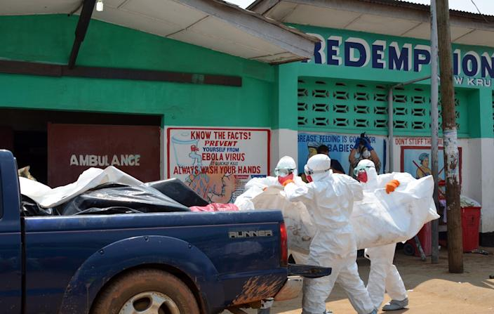 Liberian health workers wear protective suits as they remove the body of an Ebola victim from a clinic in Monrovia, on September 12, 2014 (AFP Photo/Zoom Dosso)