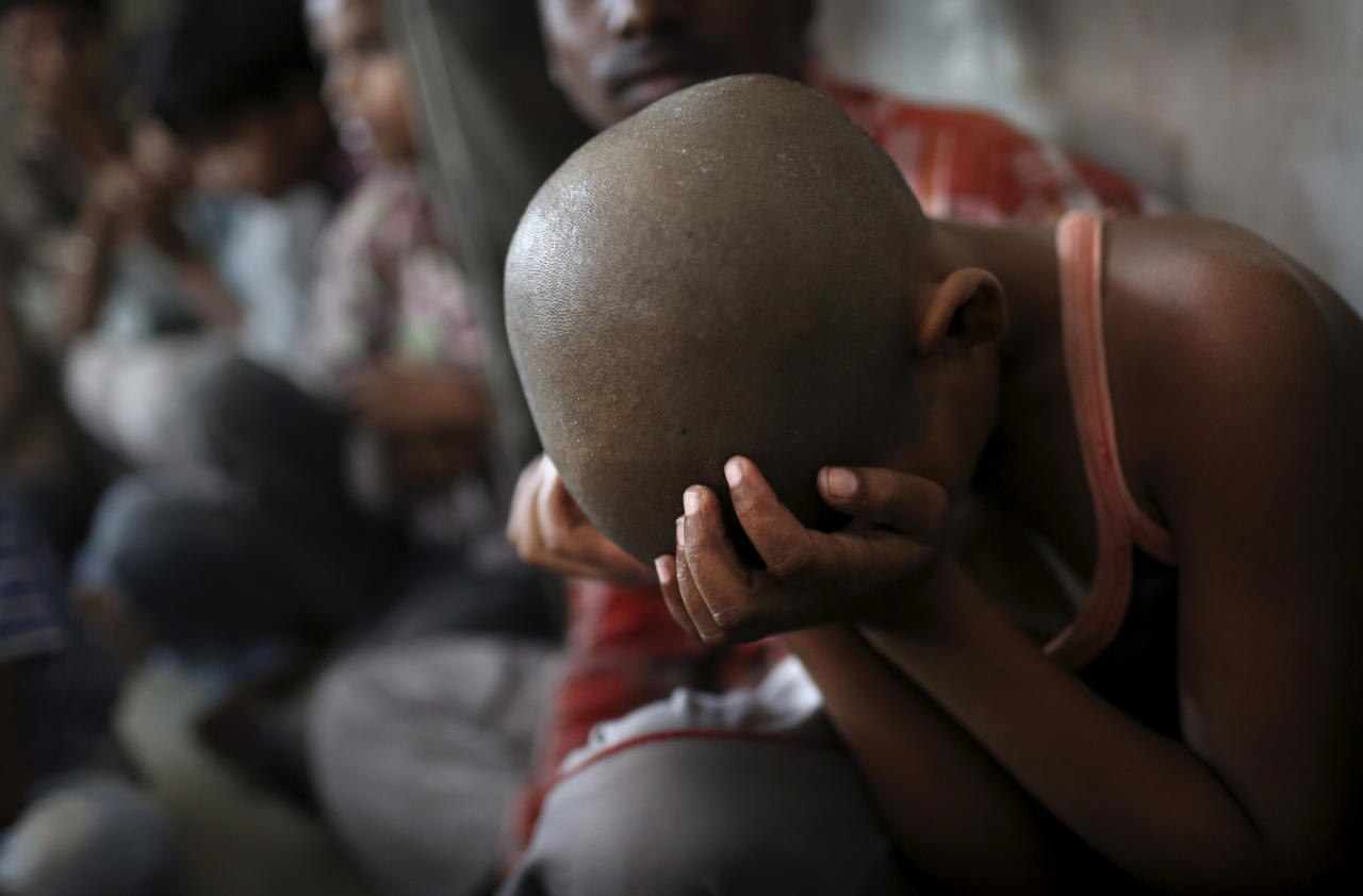 A young Indian bonded child laborer rests his head in his hands after being rescued during a raid by workers from Bachpan Bachao Andolan, or Save the Childhood Movement, at a garment factory in New Delhi, India, Tuesday, June 12, 2012. Raids on factories in the Indian capital revealed dozens of migrant kids hard at work Tuesday despite laws against child labor. Police rounded up 26 children from three textiles factories and a metal processing plant, but dozens more are believed to have escaped. Those captured had all come to New Delhi from the states of Bihar and Uttar Pradesh. (AP Photo/Kevin Frayer)