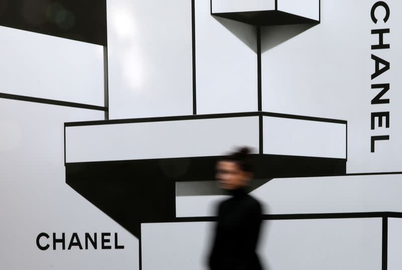 FILE PHOTO: A woman walks past the logos of French luxury goods maker Chanel in Nice