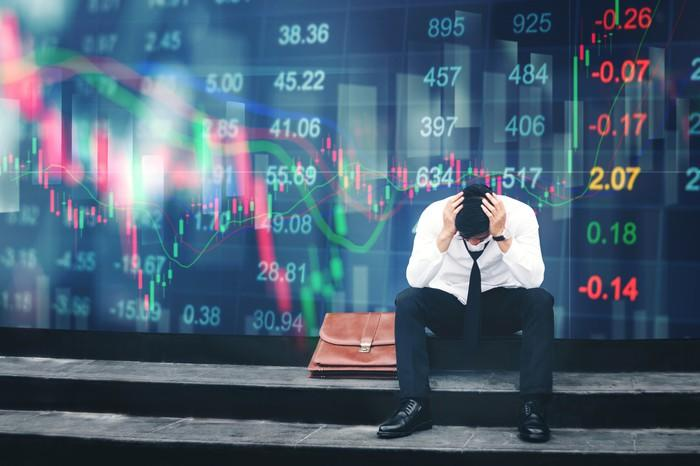 A man sitting on a step holding his head, with stock tickers behind him