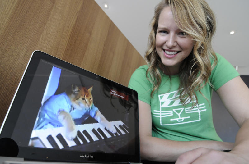 """Katie Hill, a program associate with the Walker Art Center, shows a frame from a cat video of a cat playing the piano Wednesday, Aug. 29, 2012, in Minneapolis. The Walker will present its  first """"Internet Cat Video Film Festival"""" to showcase the best in filmed feline hijinks. (AP Photo/Jim Mone)"""