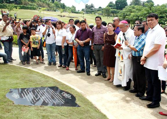 Cagayan de Oro City Archbishop Antonio Ledesma blesses the memorial for 'Sendong' victims at the Golden Haven Memorial Park in Barangay Bulua yesterday morning. Sen. Manny Villar and his wife Cynthia, Misamis Oriental second district Rep. Yevgeny Emano and Cagayan de Oro City Vice Mayor Caesar Ian Acenas graced the event.<b> GERRY GORIT</b>