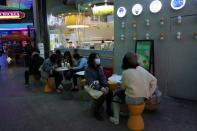 Customers sit at a tea drink store at a shopping complex in Beijing