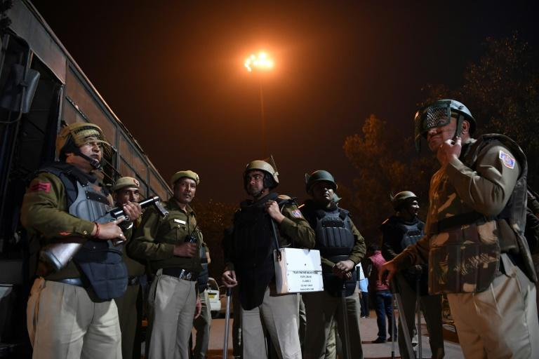 Police stand guard following clashes between supporters and opponents of a new citizenship law in New Delhi