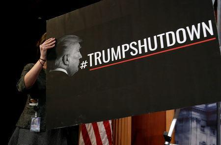 A Senate staffer places a sign blaming U.S. President Donald Trump for shutdown of the Federal Government before a news conference with Senate Minority Leader Chuck Schumer (D-NY) on Capitol Hill in Washington, U.S., January 20, 2018. REUTERS/Joshua Roberts