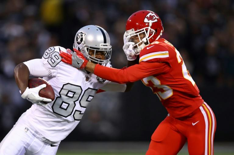 Amari Cooper (L) of the Oakland Raiders is pushed out of bounds by Phillip Gaines of the Kansas City Chiefs during their NFL game at Oakland-Alameda County Coliseum in Oakland, California, on October 19, 2017