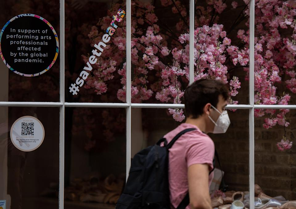 A man wearing a face mask walks past a shop in London (Getty Images)
