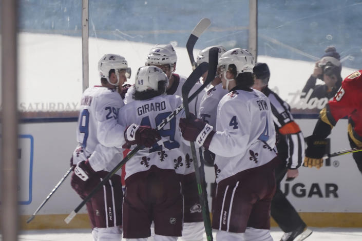 CORRECTS STATE TO NEVADA-Colorado Avalanche defenseman Samuel Girard (49) is surrounded by his teammates after scoring during the first period against the Vegas Golden Knights, at the Outdoor Lake Tahoe NHL hockey game in Stateline, Nev., Saturday, Feb. 20, 2021. (AP Photo/Rich Pedroncelli))