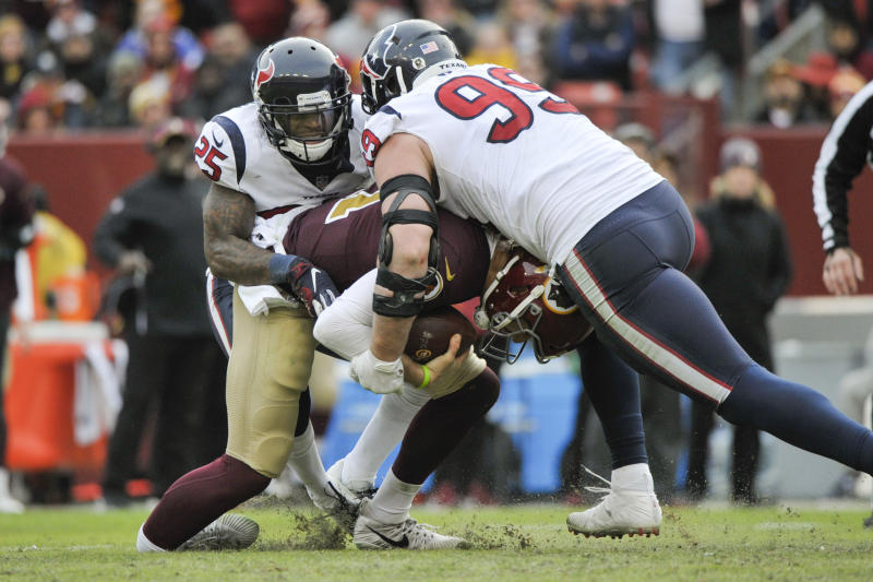 FILE - In this Nov. 18, 2018, file photo, Washington Redskins quarterback Alex Smith (11) injures his ankle as he is sacked by Houston Texans defensive end J.J. Watt (99) and Houston Texans strong safety Kareem Jackson (25) during the second half of an NFL football game, in Landover, Md. Alex Smith has finally shed the massive brace on his right leg eight months after breaking his tibia and fibula in gruesome fashion. Smith's wife, Elizabeth, posted a photo Monday, July 15, 2019, of him holding the ring external fixator in his hand. (AP Photo/Mark Tenally, File)