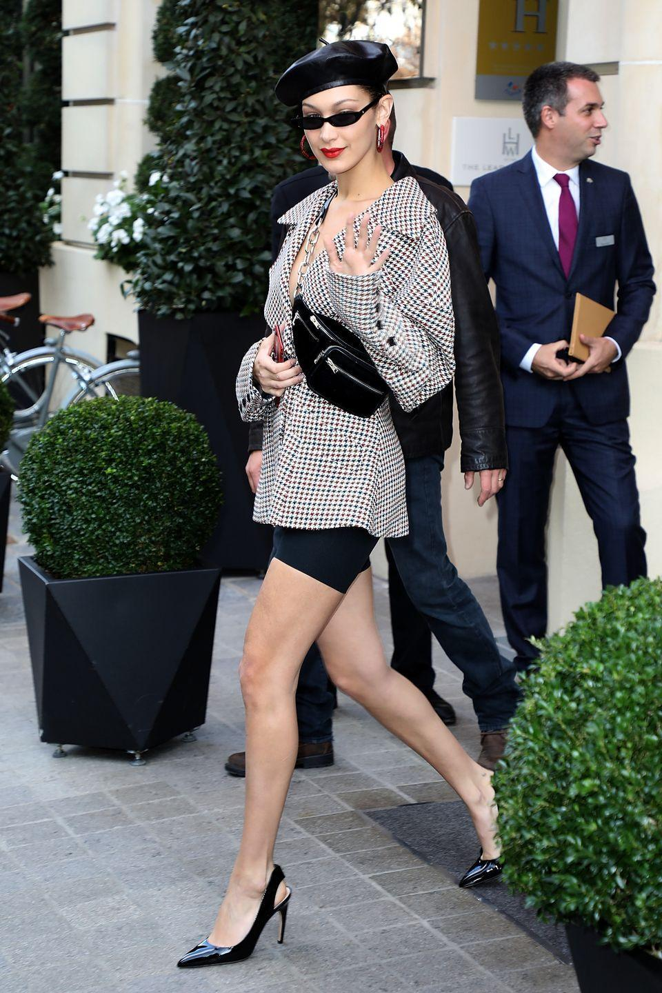 <p>In a leather beret, thin black sunglasses by Roberi & Fraud, red hoop earrings, Claudia Li blazer, Alexander Wang fanny pack, biker shorts, and Christian Dior patent leather slingback pumps while out in Paris. </p>