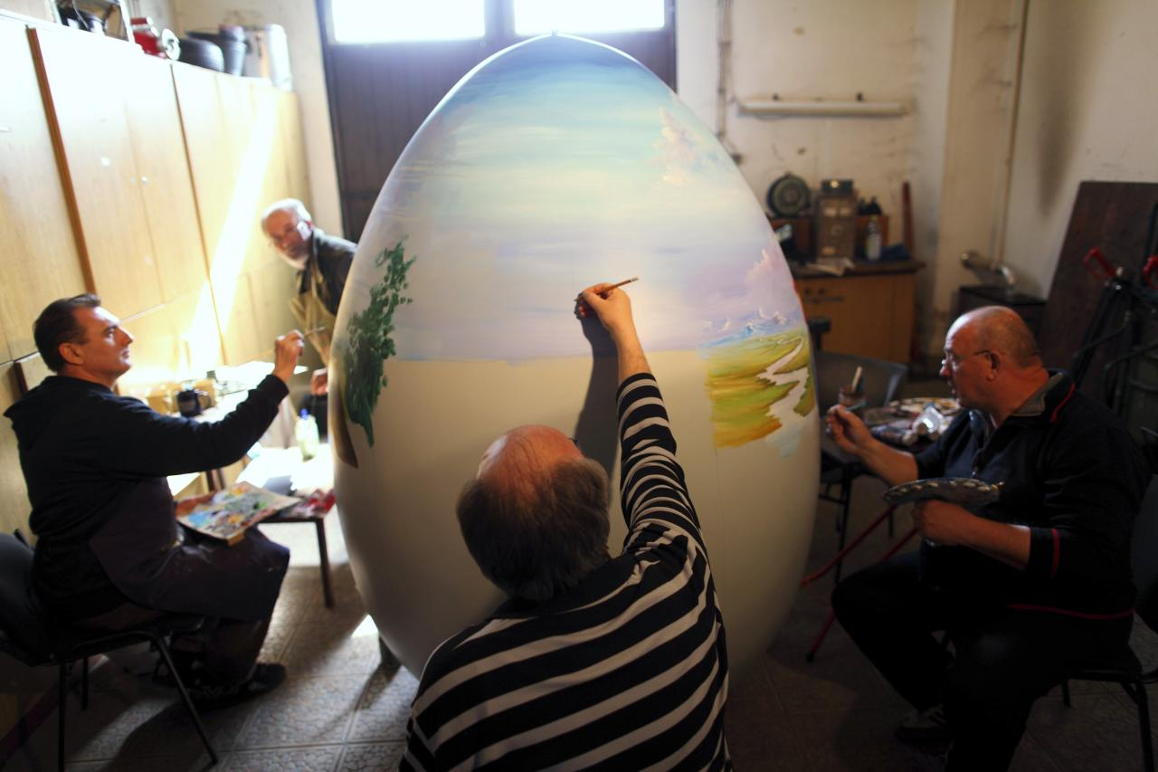 Local artists paint a two-metre-high Easter egg in the traditional naive art style in the northern Croatian town of Koprivnica March 13, 2014. The project, which started several years ago, involves painters decorating two-metre-tall polyester eggs, which are then sent to cities in the country and abroad to be displayed in public squares in time for Easter festivities. This year, three giant eggs will be painted and sent to Montenegro, Paris and Riga, the 2014 European Capital of Culture. Picture taken March 13, 2014. REUTERS/Antonio Bronic (CROATIA - Tags: SOCIETY RELIGION)