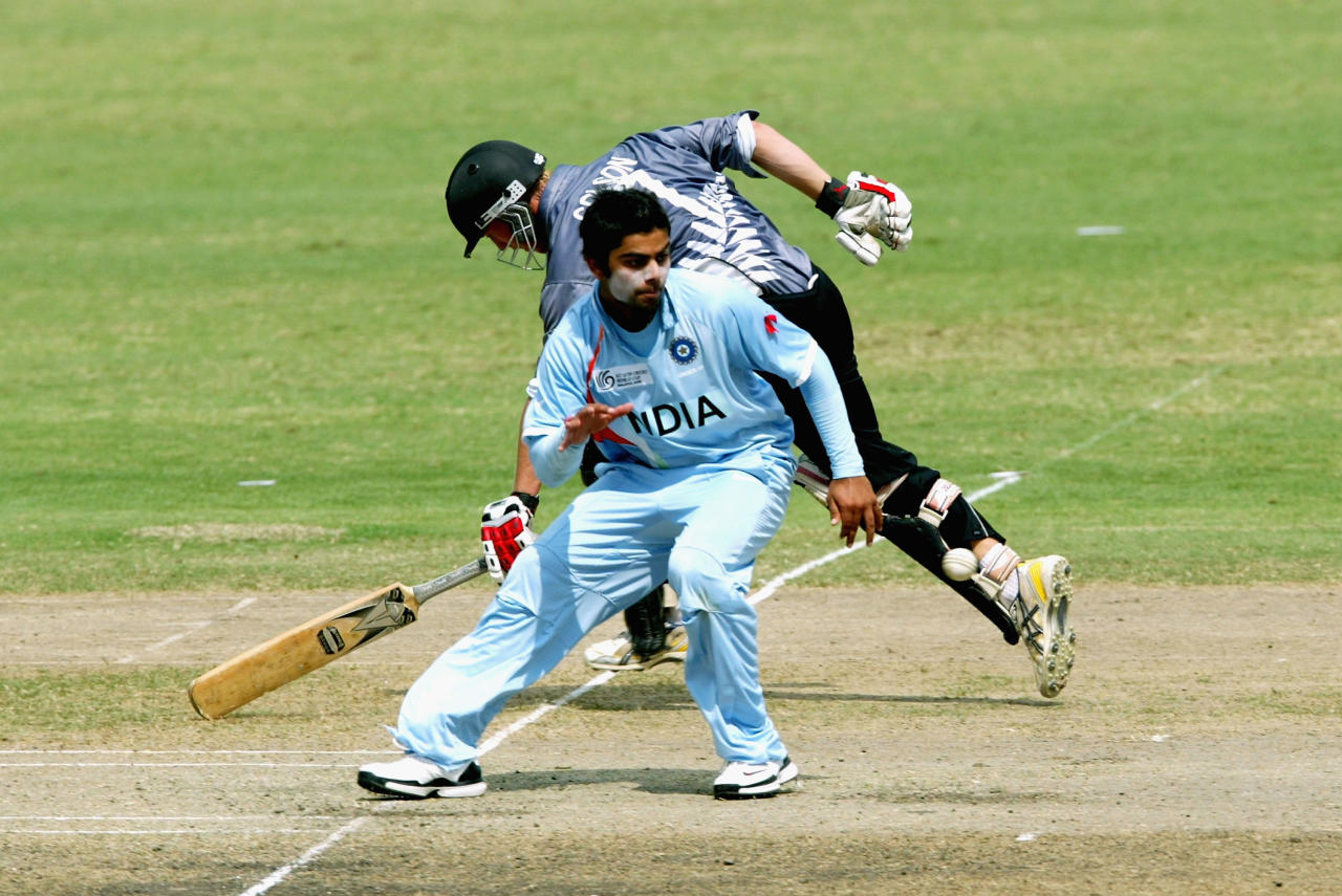 KUALA LUMPUR, MALAYSIA - FEBRUARY 27: Fraser Colson of New Zealand grounds his bat while Virat Kohli of India attempts to gather the ball during the ICC U/19 Cricket World Cup semi final match between India and New Zealand held at the Kinrara Cricket Ground on February 27, 2008 in Kuala Lumpur, Malaysia. (Photo by Stanley Chou/Getty Images)