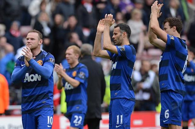 "Manchester United's English striker Wayne Rooney (L), Welsh midfielder Ryan Giggs (2nd R) and Northern Irish defender Jonny Evans (R) applaud their supporters after the English Premier League football match between Sunderland and Manchester United at The Stadium of Light in Sunderland, north-east England on May 13, 2012. AFP PHOTO/ANDREW YATES RESTRICTED TO EDITORIAL USE. No use with unauthorized audio, video, data, fixture lists, club/league logos or ""live"" services. Online in-match use limited to 45 images, no video emulation. No use in betting, games or single club/league/player publications.ANDREW YATES/AFP/GettyImages"