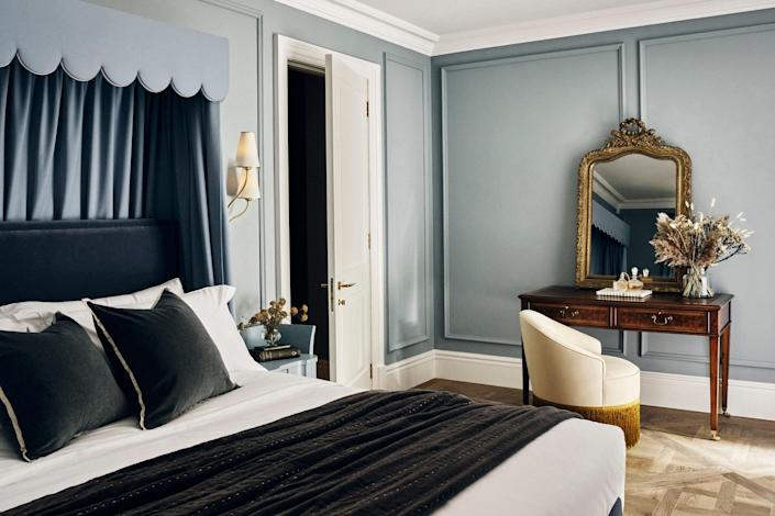 The powder blue master bedroom is a celebration of older pieces, with 1940s Italian nightstands flanking the bed and an antique English walnut dressing table.