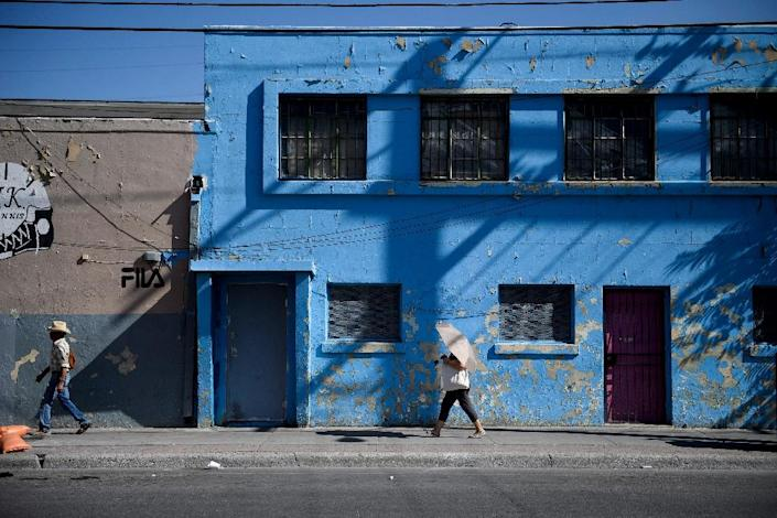 People walk through a neighborhood near the Paso del Norte border crossing in El Paso, Texas, one of the US border towns where immigration is big business (AFP Photo/Brendan Smialowski)