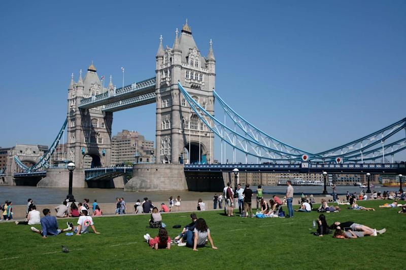People relax in the hot and sunny weather on the grass beside Tower Bridge (AFP/Getty Images)