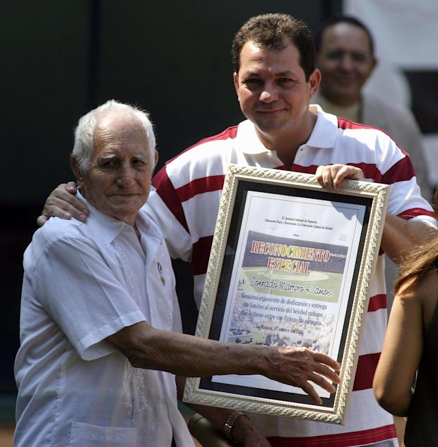 FILE - In this Oct. 12, 2003 file photo, Cuban pitcher Conrado Marrero, left, receives an award from Cuban President of the Sport Institute Humberto Rodriguez during the opening ceremony of the 35th baseball world championships in Havana, Cuba. Family members say Conrado Marrero, the oldest living former Major League Baseball player, has died in Havana. He was 102, just two days short of his 103rd birthday. Grandson Rogelio Marrero confirmed the death Wednesday afternoon, April 23, 2014. (AP Photo/Jose Goitia, File)