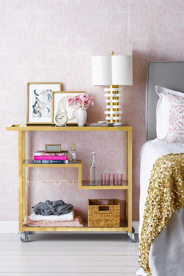 """<p>Forget the champagne (just this once): Turn a metal bar cart into a space-saving nightstand. Store your nighttime essentials — sleep masks, pillow sprays, and blankets — on the lower shelfs, and reserve the top shelf for decor that'll calm the chaos.</p><p><a class=""""body-btn-link"""" href=""""https://www.amazon.com/FirsTime-Co-70095-Francesca-12-25/dp/B07PWN41WJ/?tag=syn-yahoo-20&ascsubtag=%5Bartid%7C10055.g.2818%5Bsrc%7Cyahoo-us"""" target=""""_blank"""">SHOP BAR CARTS </a></p>"""