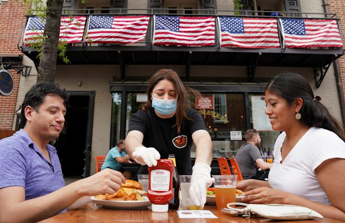 As Phase One of reopening begins in Northern Virginia today, a waitress with a face mask to protect against the coronavirus disease (COVID-19) serves diners at a restaurant in Alexandria, Virginia, U.S., May 29, 2020.  REUTERS/Kevin Lamarque