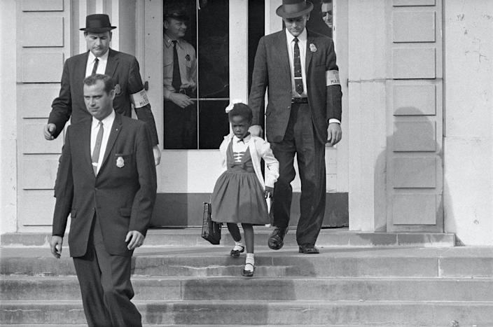 "<span class=""caption"">US deputy marshals escort 6-year-old Ruby Bridges outside William Frantz Public School in New Orleans in 1960.</span> <span class=""attribution""><a class=""link rapid-noclick-resp"" href=""https://newsroom.ap.org/detail/RubyBridgesSegregation/83ac2adbc8e147a2b80b20992ef70a97/photo?Query=Ruby%20AND%20Bridges&mediaType=photo&sortBy=arrivaldatetime:desc&dateRange=Anytime&totalCount=55&currentItemNo=28"" rel=""nofollow noopener"" target=""_blank"" data-ylk=""slk:AP Photo"">AP Photo</a></span>"