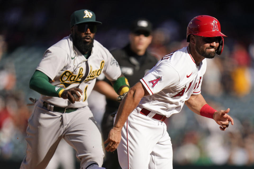 Oakland Athletics' Josh Harrison, background left, chases Los Angeles Angels' Jack Mayfield to tag him out during the 10th inning of a baseball game Sunday, Sept. 19, 2021, in Anaheim, Calif. (AP Photo/Jae C. Hong)