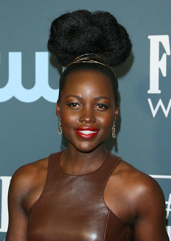 """<p>Lupita Nyong'o's wore her natural hair in a big braided bun that looked like a cloud. Her hairstylist Vernon Francois achieved the sky-high look with the help of natural hair extensions and <a href=""""http://ulta.ztk5.net/c/249354/164999/3037?subId1=IS%2CCriticsChoiceAwardsHair%2Clukase%2C%2CIMA%2C3513890%2C202001%2CI&u=https%3A%2F%2Fwww.ulta.com%2Ftotal-results-high-amplify-flexible-hold-hairspray%3FproductId%3DxlsImpprod6490188"""" target=""""_blank"""">Matrix Total Results Amplify Flexible Hold Hairspray</a>. """"It is an all day humidity resistant root lifter and a must-have for maintaining body throughout the day and night,"""" he said of the key product behind the <em>Us </em>star's updo. """"It easily washes out and leaves no build-up which is important for kinky hair types!"""" A gold wire headband finished off the look. </p>"""