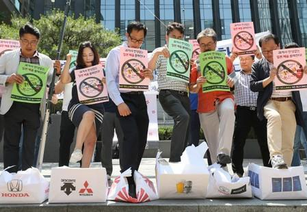 South Korean merchants step on boxes bearing logos of Japanese products during a rally to declare a boycott of Japanese goods in Seoul