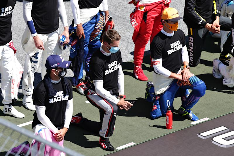 SPIELBERG, AUSTRIA - JULY 05: Sergio Perez of Mexico and Racing Point, Romain Grosjean of France and Haas F1 and Lando Norris of Great Britain and McLaren F1 take a knee in support of the Black Lives Matter movement before the Formula One Grand Prix of Austria at Red Bull Ring on July 05, 2020 in Spielberg, Austria. (Photo by Peter Fox/Getty Images)