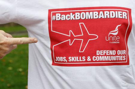 Member of Britain's Unite trade union presents a t-shirt with slogans during a protest outside the Houses of Parliament in support of Bombardier workers in London