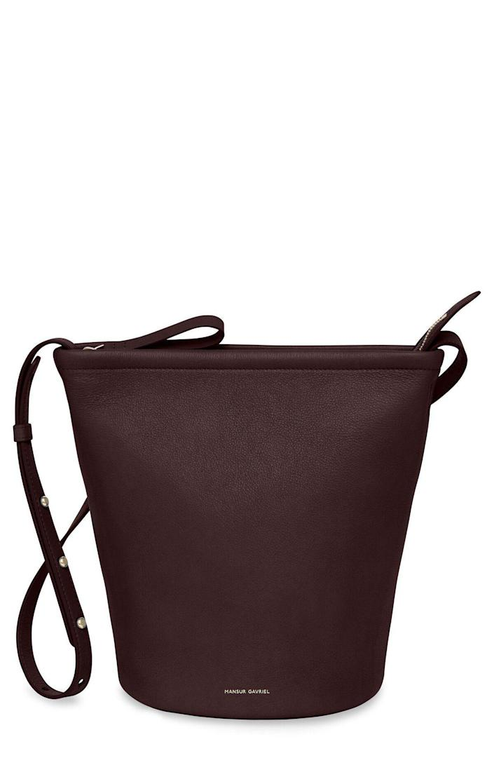 """<p><strong>Mansur Gavriel</strong></p><p>amazon.com</p><p><strong>$595.00</strong></p><p><a href=""""https://www.amazon.com/dp/B08XK9QQH1?tag=syn-yahoo-20&ascsubtag=%5Bartid%7C10056.g.36363979%5Bsrc%7Cyahoo-us"""" rel=""""nofollow noopener"""" target=""""_blank"""" data-ylk=""""slk:Shop Now"""" class=""""link rapid-noclick-resp"""">Shop Now</a></p><p>Swap out her go-to tote for this durable zipper closure bucket bag that can be worn as a crossbody or adjusted to wear on her shoulder. </p>"""