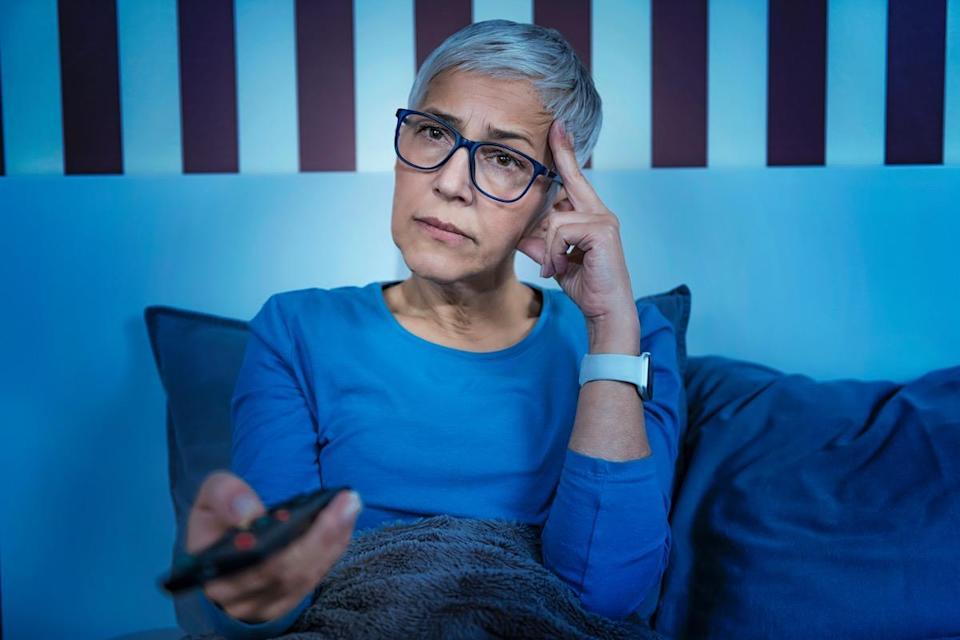 Senior woman in bed, watching TV late at night.